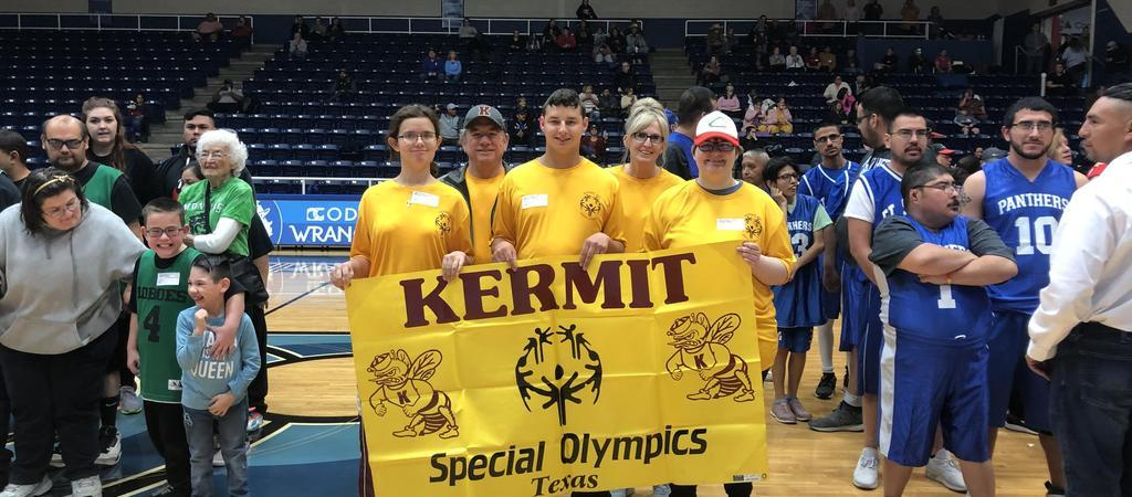 "Four students in yellow shirts hold up a sign that says, ""Kermit Special Olympics, Texas."""