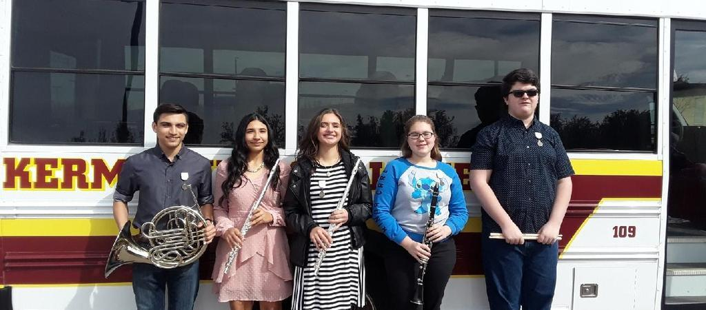 Five students line up against a school bus holding their band instruments.